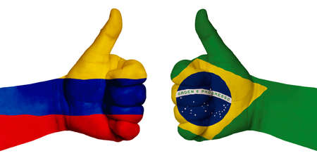 Politics and finance concept. Two hands with a raised finger. They portray the gesture class, managed to negotiate. On the hands of the image of the flags of the countries, Brazil and Colombia