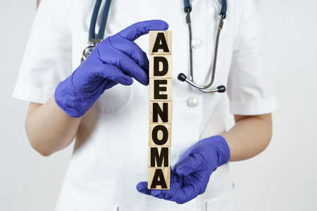 Medicine and health concept. The doctor holds cubes in his hands on which it is written - ADENOMA