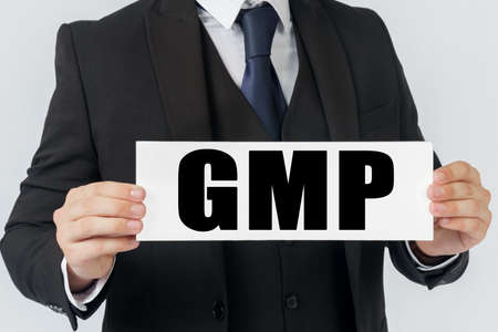 Business and finance concept. A businessman holds a sign in his hands which says GMP - GOOD MANUFACTURING PRACTICE Imagens