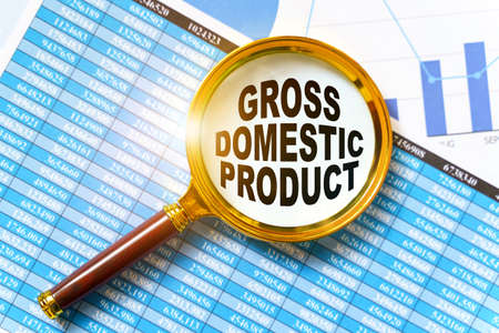Finance and business concept. Financial reports, charts and a magnifying glass are on the table. Inside the magnifier there is an inscription - GROSS DOMESTIC PRODUCT