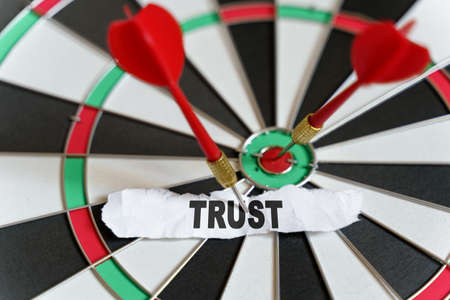 Business and finance concept. A piece of paper with the text is nailed to the target with a dart - TRUST Foto de archivo