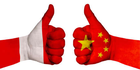 Politics and finance concept. Two hands with a raised finger. They portray the gesture class, managed to negotiate. On the hands of the image of the flags of countries, China and Peru