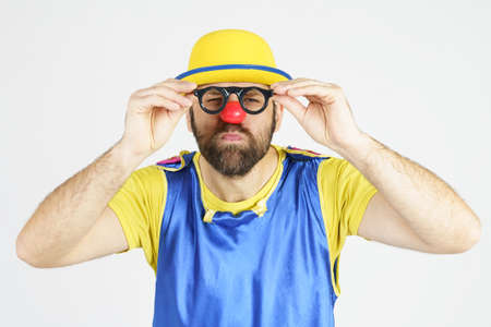 Holiday concept. A clown in a bright blue and yellow suit adjusts his glasses