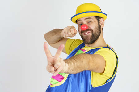 Holiday concept. A clown in a bright blue and yellow suit shows a slingshot with his hands - aims Foto de archivo