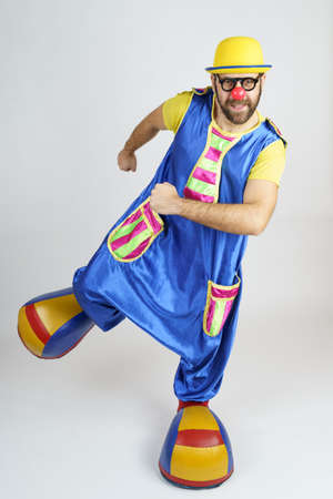 Holiday concept. The clown is a man in a bright blue and yellow suit, glasses and a hat, playing emotionally.