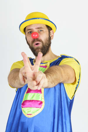 Holiday concept. A clown in a bright blue and yellow suit shows a slingshot with his hands - aims