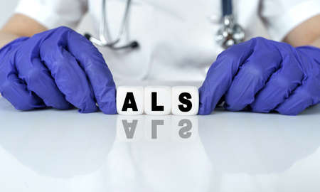Medicine and health concept. The doctor put together a word from cubes ALS. amyotrophic lateral sclerosis