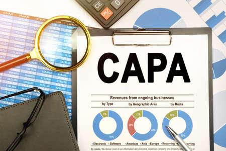 Business and finance concept. On the table are charts with reports, a notebook, a magnifying glass and a document with the inscription - CAPA