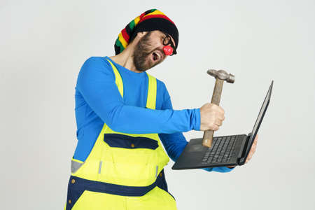 Humor and communication concept. A clown in a bright suit holds a laptop in his hands, hits it with a hammer Foto de archivo