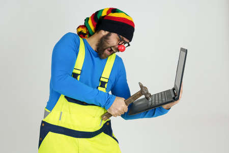 Humor and communication concept. A clown in a bright suit holds a laptop in his hands, hits it with a hammer