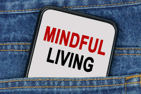 Business and finance concept. In a pocket of jeans there is a smartphone on the screen of which the text - MINDFUL LIVING