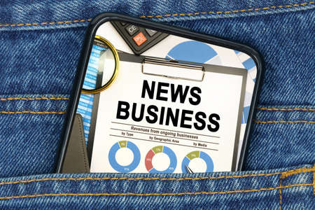 Business and finance concept. In a pocket of jeans there is a smartphone on the screen of which the text - NEWS BUSINESS