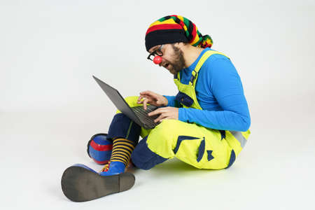 Celebration and communication concept. A clown in bright clothes sits on the floor and communicates via a laptop.
