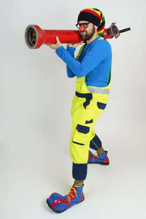 Holiday and fun concept. The clown firefighter holds a fire pump in his hands like a grenade launcher.
