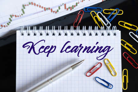 Finance and economics concept. On the desktop are a forex chart, paper clips, a pen and a notebook in which it is written - Keep learning