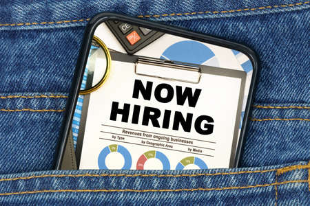 Business and finance concept. In a pocket of jeans there is a smartphone on the screen of which the text - NOW HIRING