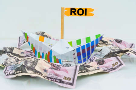 Business and finance concept. A paper boat from a business graph floats on a sea of money. The text is written on the flag - ROI