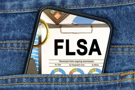 Business and finance concept. In a pocket of jeans there is a smartphone on the screen of which the text - FLSA