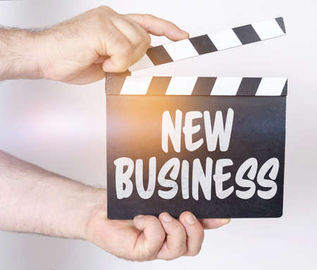 Business and finance concept. On a white background, a man holds a clapperboard in his hands on which it is written - NEW BUSINESS