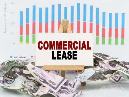 Business and finance concept. Among financial charts and money is a sign with the text - COMMERCIAL LEASE