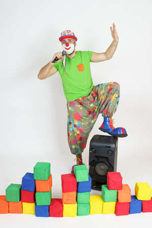 Holiday and fun concept. The clown is holding a microphone, singing. Nearby are colorful cubes and a column. Isolated on white