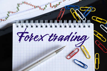 Finance and economics concept. On the desktop are a forex chart, paper clips, a pen and a notebook in which it is written - Forex trading