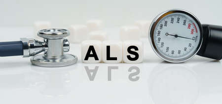 Medicine concept. On a reflective white surface lies a stethoscope and cubes with the inscription - ALS