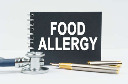 Medicine and health concept. On a white background lies a stethoscope, a pen and a black notebook with the inscription - FOOD ALLERGY