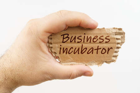 Business and finance. A man holds a cardboard in his hand on which it is written - Business incubator