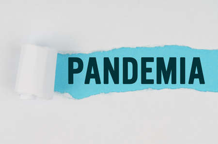 Medicine and health concept. In the middle of a white sheet of paper, a tear is made under which, on a blue background, the inscription - PANDEMIA 免版税图像