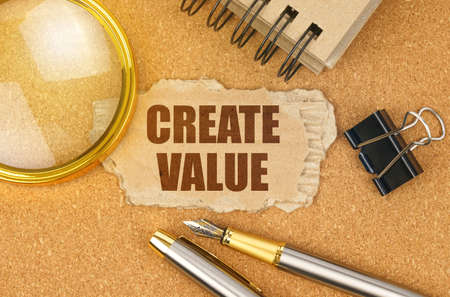 Business and finance concept. On the table are office items and a cardboard with the inscription - CREATE VALUE