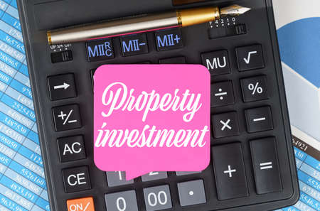 Finance and economics concept. On the desktop are charts, reports, a calculator and a sheet for notes on which it is written - Property investment