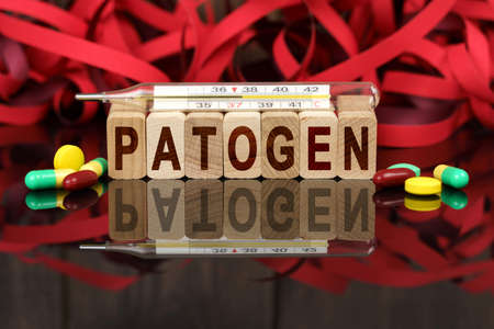 Medicine and health concept. On the surface are visible pills, a thermometer, wooden dies and their reflections on which it is written - PATOGEN