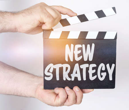 Business and finance concept. On a white background, a man holds a clapperboard in his hands on which it is written - NEW STRATEGY
