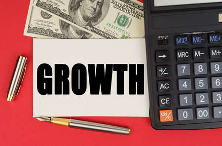 Business and finance concept. On a red background, among the money, a calculator and a pen lies a sign with the text - GROWTH