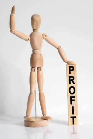 Business and medicine. The wooden man raised his hand, and under his left hand he has cubes with the inscription - PROFIT 免版税图像