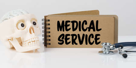 Medicine and health concept. On the table lies a skull, a stethoscope and a notebook with the inscription - MEDICAL SERVICE