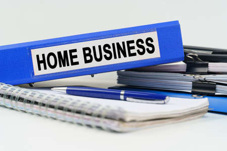 Business and finance concept. On the table are a notebook, a pen, documents and a folder with the inscription - HOME BUSINESS