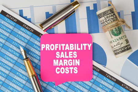 Business and finance concept. Among the financial statements and charts is a note with the text - PROFITABILITY SALES MARGIN COSTS