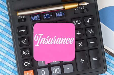 Finance and economics concept. On the desktop are charts, reports, a calculator and a sheet for notes on which it is written - Insurance Archivio Fotografico
