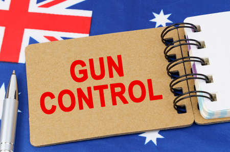 Law and justice concept. Against the background of the flag of Australia lies a notebook with the inscription - GUN CONTROL