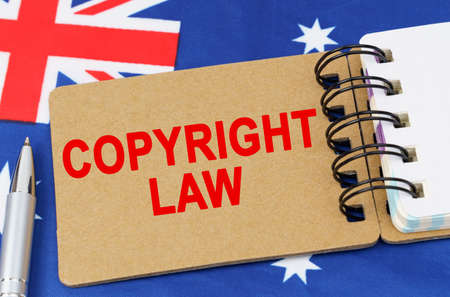 Law and justice concept. Against the background of the flag of Australia lies a notebook with the inscription - COPYRIGHT LAW