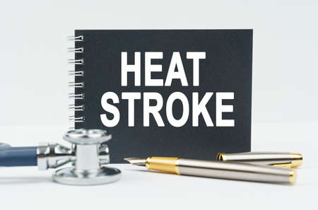 Medicine and health concept. On a white background lies a stethoscope, a pen and a black notebook with the inscription - HEAT STROKE