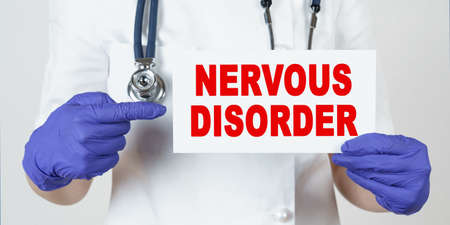 Medicine and health concept. The doctor points his finger at a sign that says - NERVOUS DISORDER 免版税图像