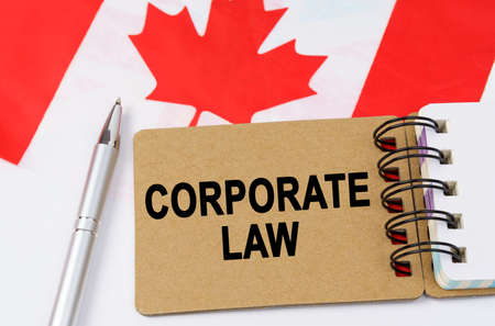 Law and justice concept. Against the background of the flag of Canada lies a notebook with the inscription - CORPORATE LAW