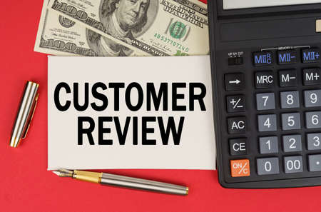 Business and finance concept. On a red background, among the money, a calculator and a pen lies a sign with the text - CUSTOMER REVIEW