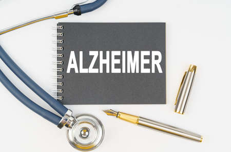 Medicine and health. On a white background lie a stethoscope, a pen and a notebook with the inscription - ALZHEIMER