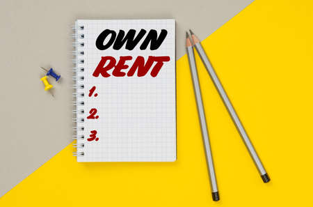 Business and finance. On a yellow-gray background are pencils, buttons and a notebook in which it is written - OWN RENT