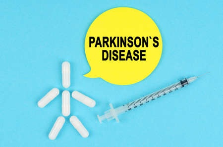 Medicine and health concept. Syringe, human figure made of pills and paper sticker with the inscription - PARKINSONS DISEASE