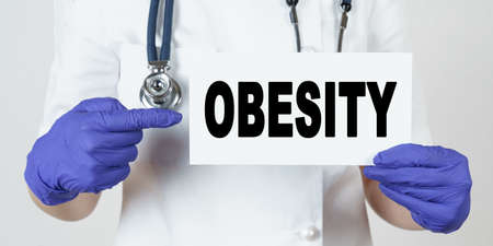 Medicine and health concept. The doctor points his finger at a sign that says - OBESITY